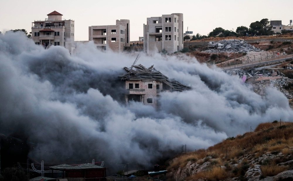 This picture taken on Monday shows the demolition of a Palestinian building which was under construction, in the the Palestinian village of Sur Baher in East Jerusalem. — AFP