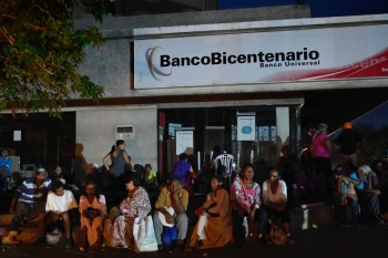 People get ready to spend the night outside a bank in Maracaibo, Zulia State, Venezuela on Monday to collect their pensions the next day, as parts of the country, including the capital Caracas, were hit by a massive power cut. -AFP