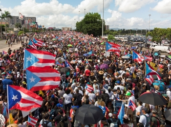 People gather along a main highway during a protest calling for the resignation of Governor Ricardo Rossello in San Juan, Puerto Rico on Monday. -Reuters