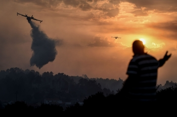 A villager gestures as fire squads drop water over a wildfire at sunset in Chaveira in Macao in central Portugal on Tuesday. — AFP