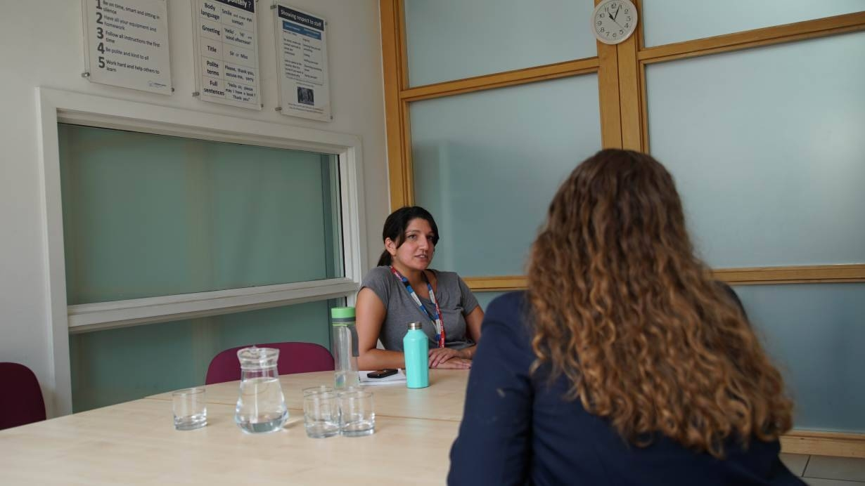 Rebecca Maharaj, a mental health professional with Britain's National Health Service, talks to a high school student in London in this July 4, 2019 file photo. — Thomson Reuters Foundation