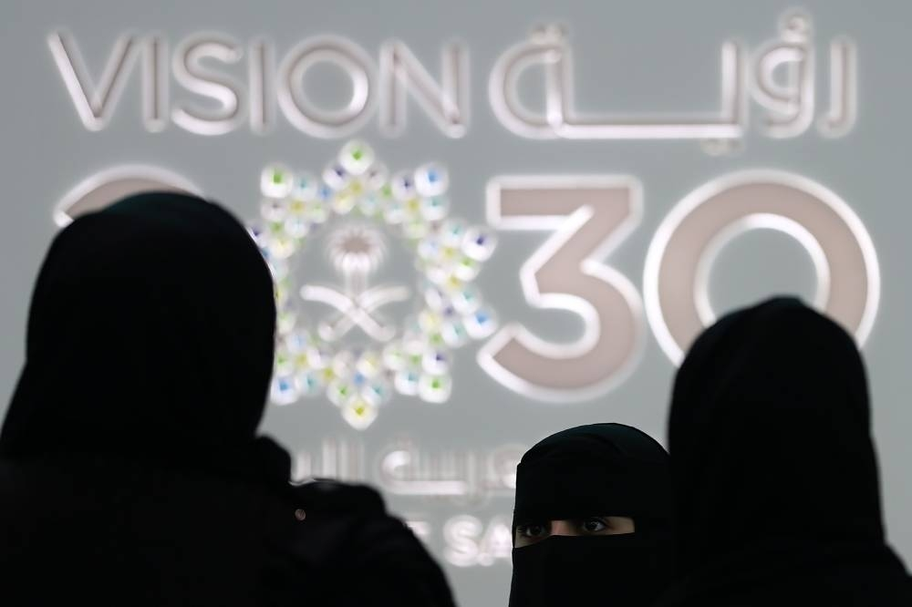 Saudi women stand next to the Saudi pavilion (vision 2030) at the Gitex 2018 exhibition at the Dubai World Trade Center in Dubai on October 2018. AFP
