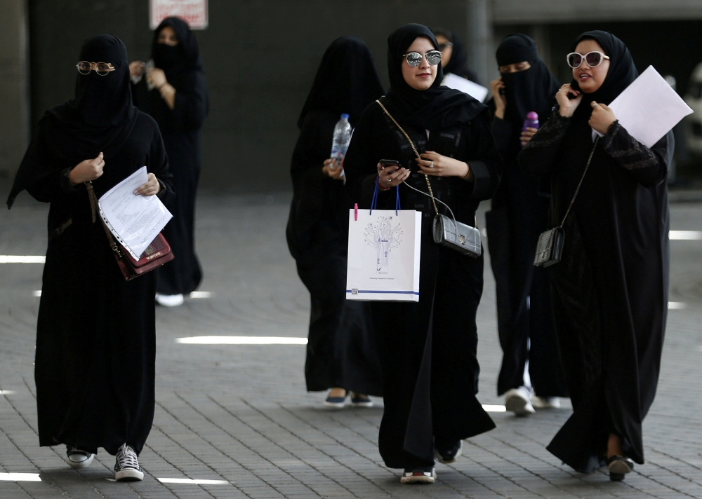Saudi students walk at the exhibition to guide job seekers at Glowork Women's Career Fair in Riyadh in this Oct. 2, 2018 file photo. — Reuters