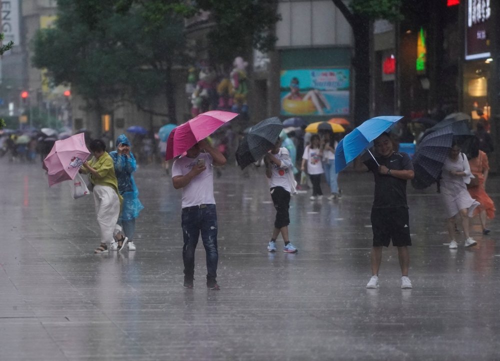 People walk in the rainstorm as typhoon Lekima approaches in Shanghai, China, on Saturday. — Reuters