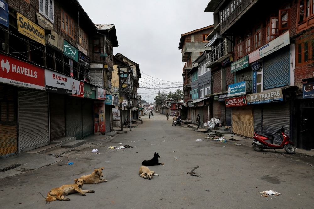 Dogs rest on an empty street during restrictions after the scrapping of the special constitutional status for Kashmir by the government, in Srinagar, India, on Sunday. — Reuters