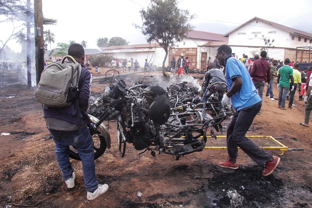 Two men carry the remains of a burned out motorbike after a fuel tanker exploded Saturday, in Morogoro, 200 km west of the Tanzanian capital Dar es Salaam. — AFP