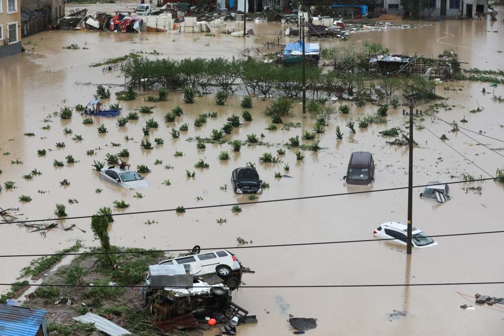Cars are partially submerged in floodwaters after Typhoon Lekima hit Dajing town in Wenzhou, Zhejiang province, China, on Saturday. — Reuters