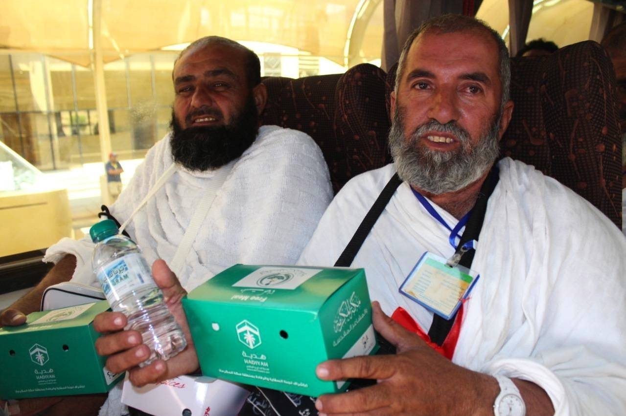 Pilgrims receive packages of ready meals and water bottles. — SPA