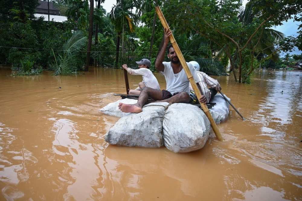 Residents use improvised materials as floodwaters submerged areas of Ye township in Mon State, Myanmar, on Sunday. — AFP
