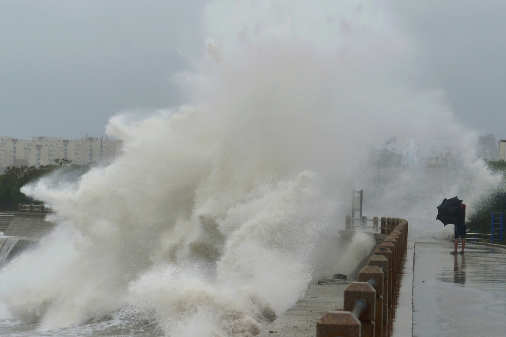 A wave brought by typhoon Lekima breaks on the shore next to a pedestrian in Qingdao, Shandong province, China, on Sunday. — Reuters
