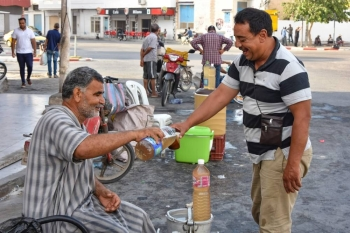 A customer buys a glass of legmi from a street vendor, a coveted date palm drink, in the southwestern Tunisian town of Gabes on July 18. -AFP