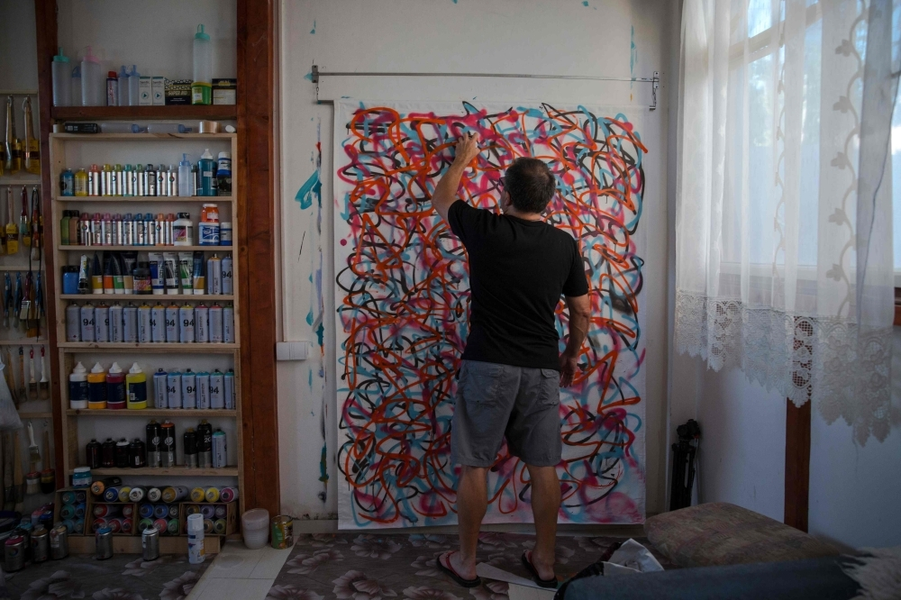 US artist Jeff Ross works on his drawing, in Pancevo, near Belgrade on Friday. -AFP