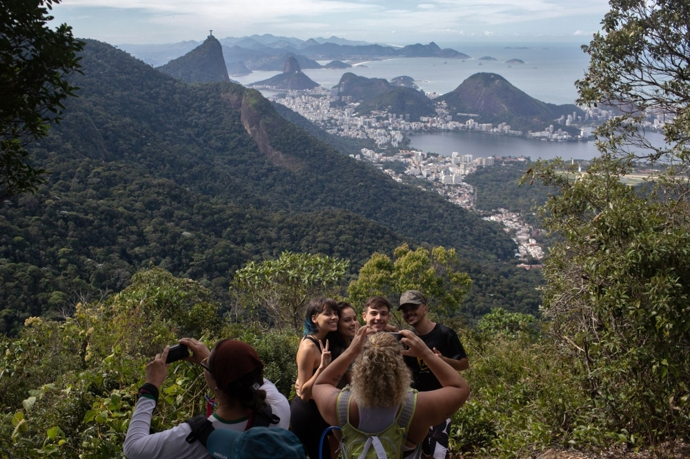 People take photos as they walk along a hiking trail -part of a projected 8,000-kilometer trail across Brazil, which will be one of the losgest in the Americas- in Rio de Janeiro, Brazil, on July 21, 2019.  -AFP