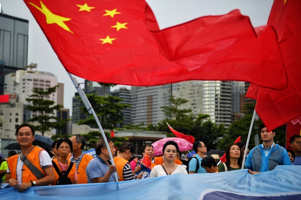 Pro-Beijing supporters wave the China national flag during a pro-government rally at Tamar Park in Hong Kong on Saturday. -AFP