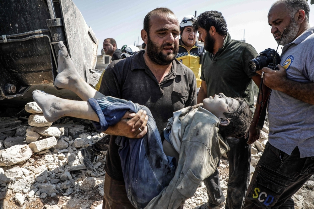 A Syrian carries the body of a child at the site of a reported regime air strike on the village of Deir Sharqi on the eastern outskirts of Maaret al-Numan in Syria's northern province of Idlib on Saturday. -Courtesy photo