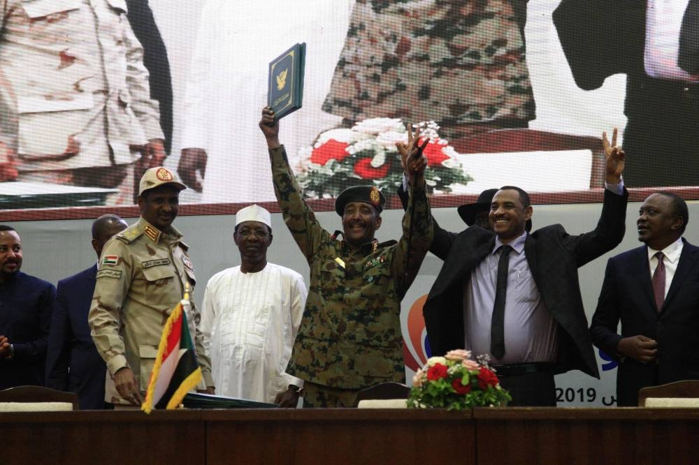 Sudan's protest leader Ahmad Rabie (2nd-right) flashes the victory sign alongside Gen. Abdel Fattah Al-Burhan (center), the chief of Sudan's ruling Transitional Military Council (TMC), during a ceremony where they signed a