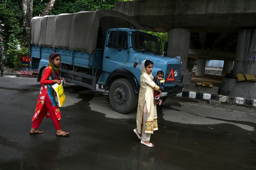 Kashmiri pedestrians walk past a security personnel vehicle in Srinagar on Saturday. Seventeen out of around 100 telephone exchanges were restored in the restive Kashmir Valley, the local police chief told AFP, after an almost two-week communications blackout. — AFP