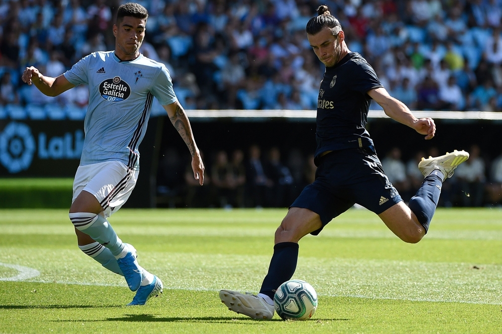 Real Madrid's Welsh forward Gareth Bale (R) challenges Celta Vigo's Uruguayan defender Lucas Olaza during the Spanish League football match between Celta Vigo and Real Madrid at the Balaidos Stadium in Vigo, on Saturday. — AFP