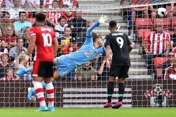 Southampton's English goalkeeper Angus Gunn dives but cannot reach the shot from Liverpool's Senegalese striker Sadio Mane (not pictured) as Liverpool take the lead during the English Premier League football match between Southampton and Liverpool at St. Mary's Stadium in Southampton, southern England, on Saturday. — AFP
