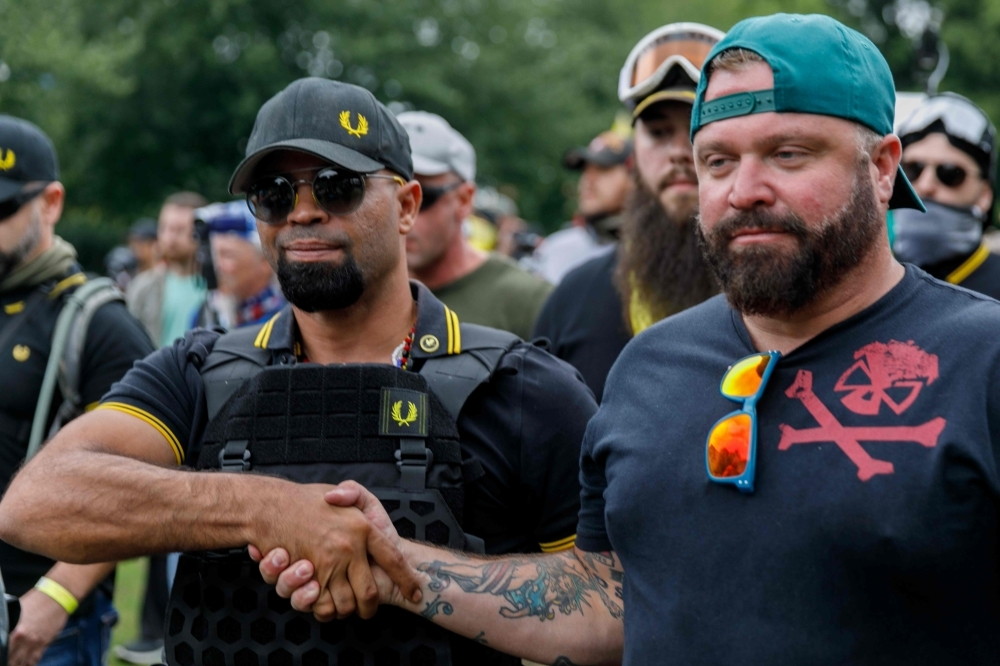 Leader of the Proud Boys Enrique Tarrio (L) and rally organizer Joe Biggs (R) congratulate each other as they return to the march starting-point over the Hawthorn Bridge as