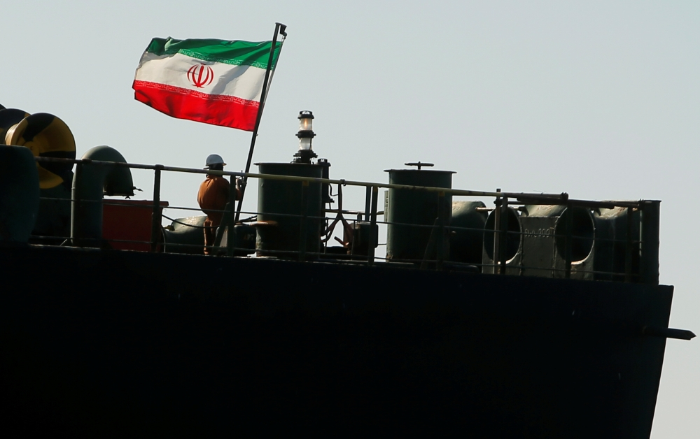 A crew member raises the Iranian flag on Iranian oil tanker Adrian Darya 1, previously named Grace 1, as it sits anchored after the Supreme Court of the British territory lifted its detention order, in the Strait of Gibraltar, Spain, on Sunday. -Reuters