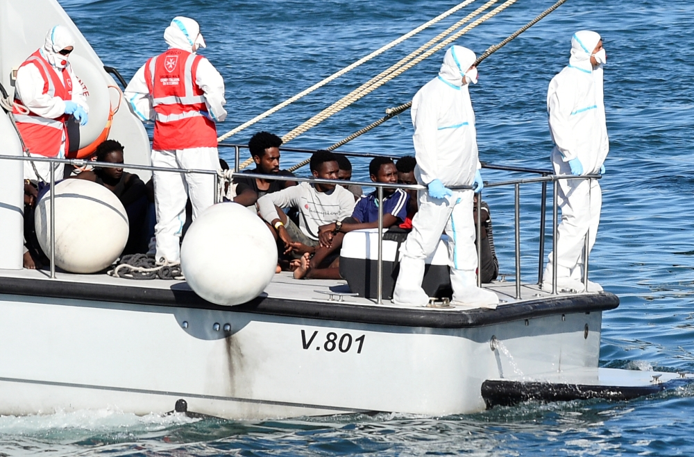 Minors who were among migrants stranded on the Spanish migrant rescue ship Open Arms are pictured before disembarking from an Italian Finance Police boat, in Lampedusa, Italy on Sunday. -Reuters