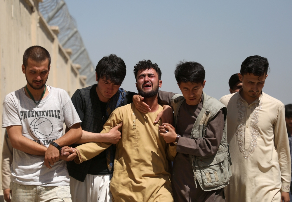 An Afghan mourns during the funeral of his brother. — Reuters