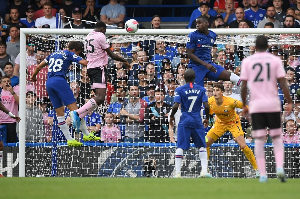 Leicester City's Nigerian midfielder Wilfred Ndidi (2L) jumps to scores the equalizing goal during the English Premier League football match between Chelsea and Leicester City at Stamford Bridge in London, on Sunday. — AFP