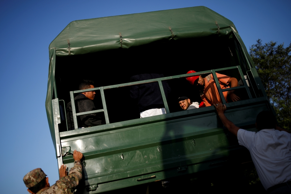 Venezuelan migrants get on military trucks to get a free ride from the Ecuadorian-Peruvian border service to Tumbes, after processing their documents, on the outskirts of Tumbes, Peru June 15, 2019. -Reuters