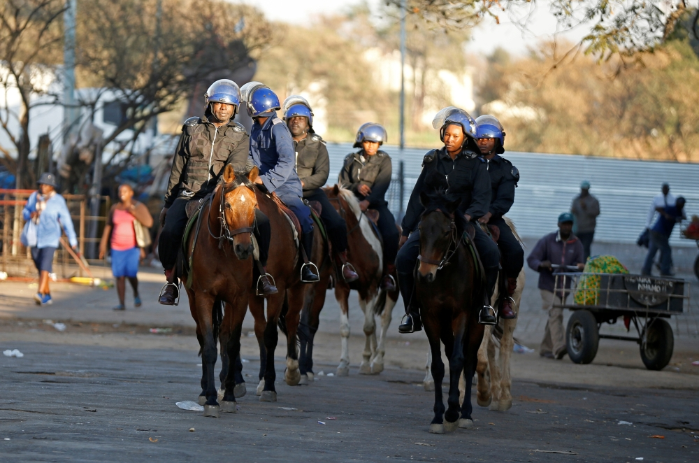 Riot police officers ride horses as they patrol the streets in Bulawayo, Zimbabwe, on Monday. -Reuters