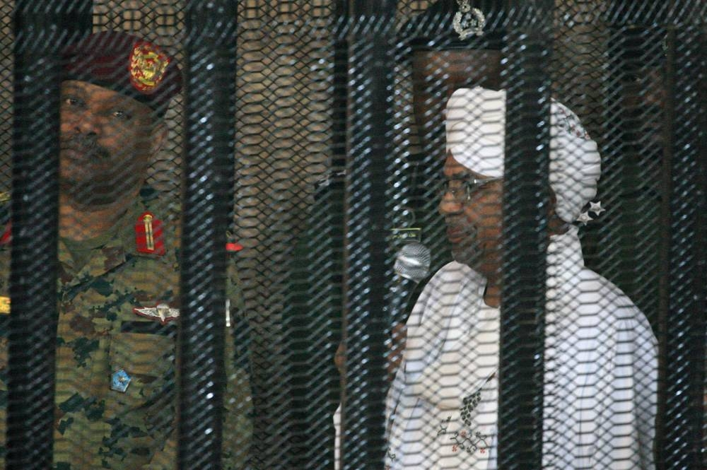Sudan's deposed military ruler Omar Al-Bashir stands in a defendant's cage during the opening of his corruption trial in Khartoum, Monday. — AFP
