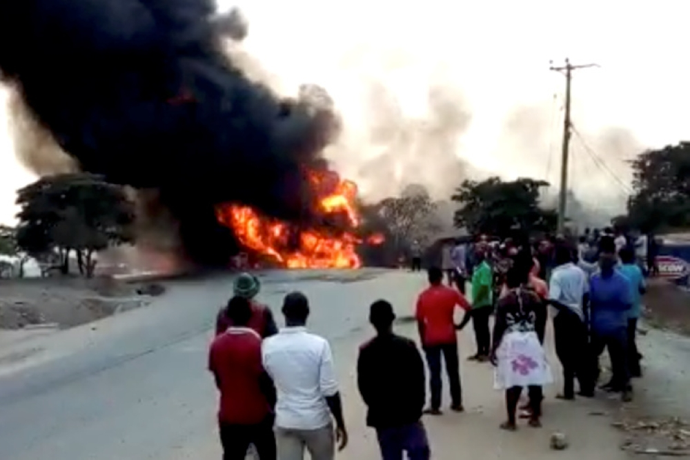 People look towardss a fire following a fuel truck collision in Rubirizi, Uganda, on Sunday in this still image taken from social media video. — Reuters