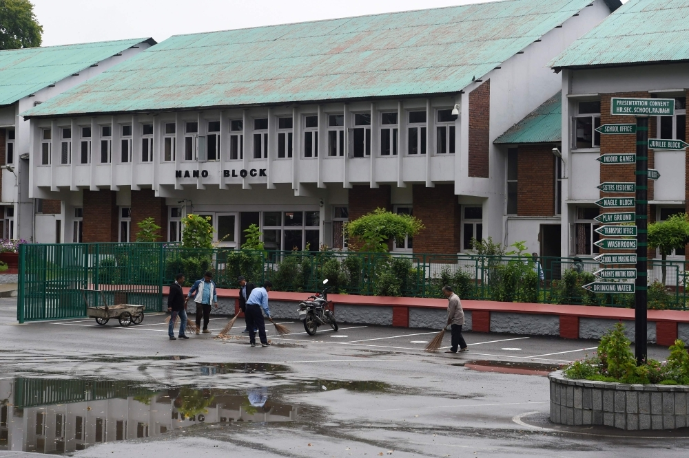 Workers clean the campus of an closed school in Srinagar, India, on Monday. — AFP