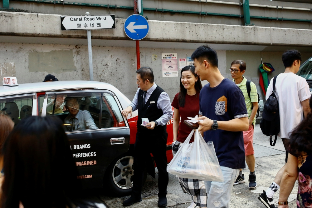 People walk in a street in the Wan Chai neighborhood in Hong Kong, China, on Monday. — Reuters