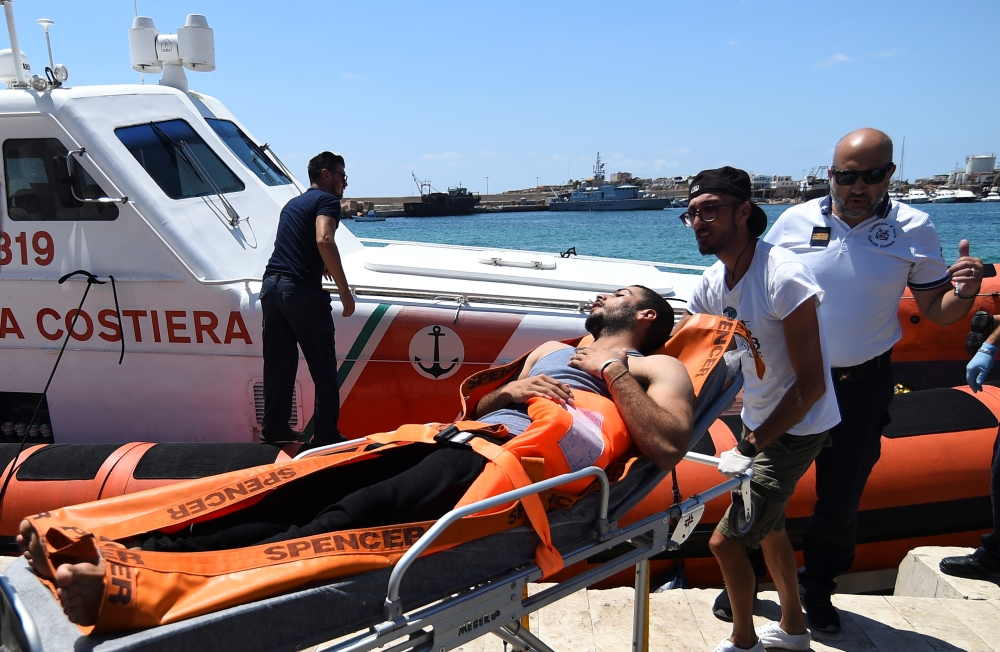 A migrant who jumped off the Spanish rescue ship Open Arms is carried on a stretcher, in Lampedusa, Italy, on Tuesday. — Reuters