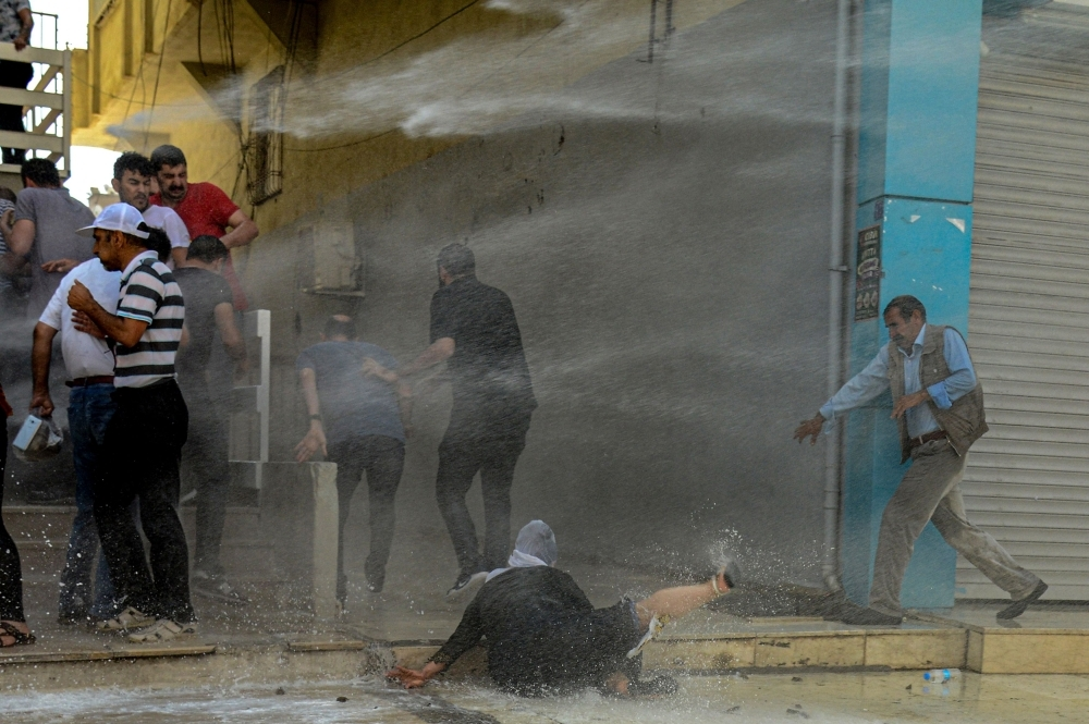 Demonstrators are hit by water cannon during a protest against the replacement of Kurdish mayors with state officials in three cities, in Diyarbakir, in eastern Turkey, on Tuesday. — AFP