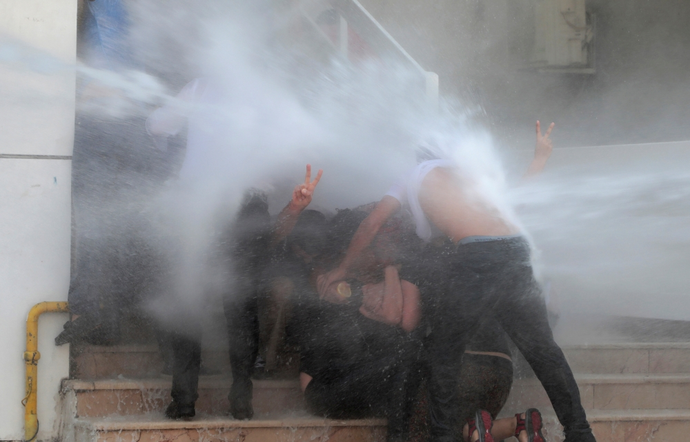 Police use a water cannon to disperse demonstrators during a protest against the replacement of Kurdish mayors with state officials in three cities, in Diyarbakir, Turkey, on Tuesday. — Reuters