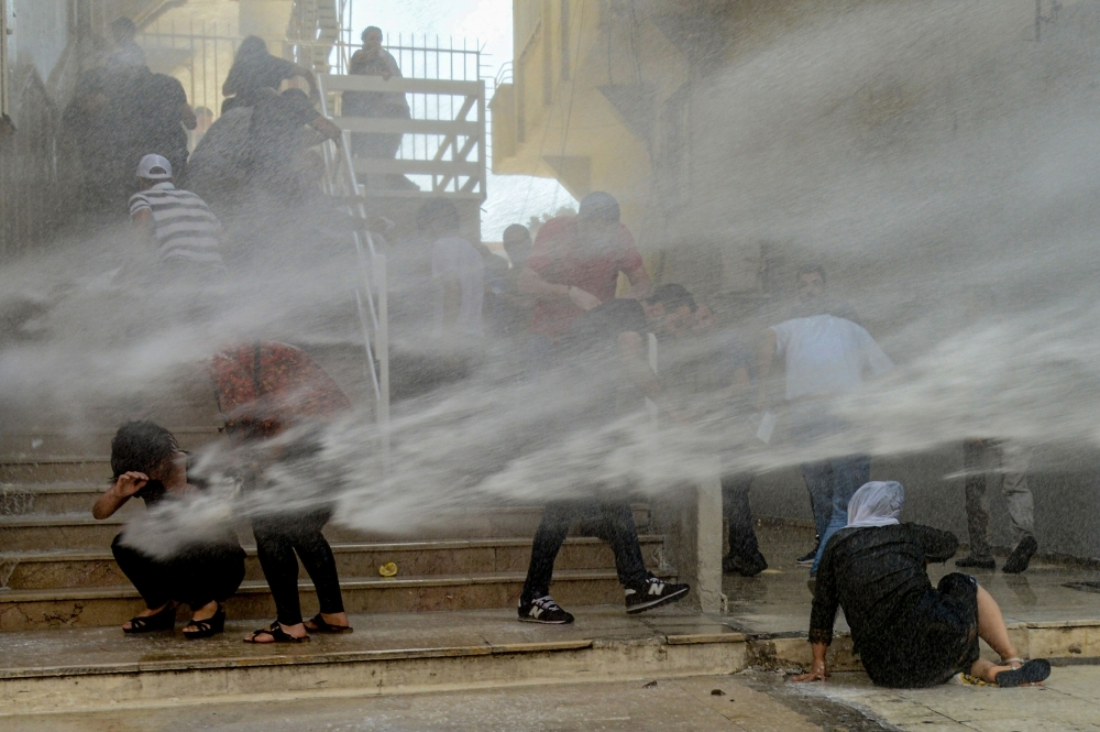 Demostrators are hit by water cannon during a protest against the replacement of Kurdish mayors with state officials in three cities, in Diyarbakir, in eastern Turkey on Tuesday. — AFP