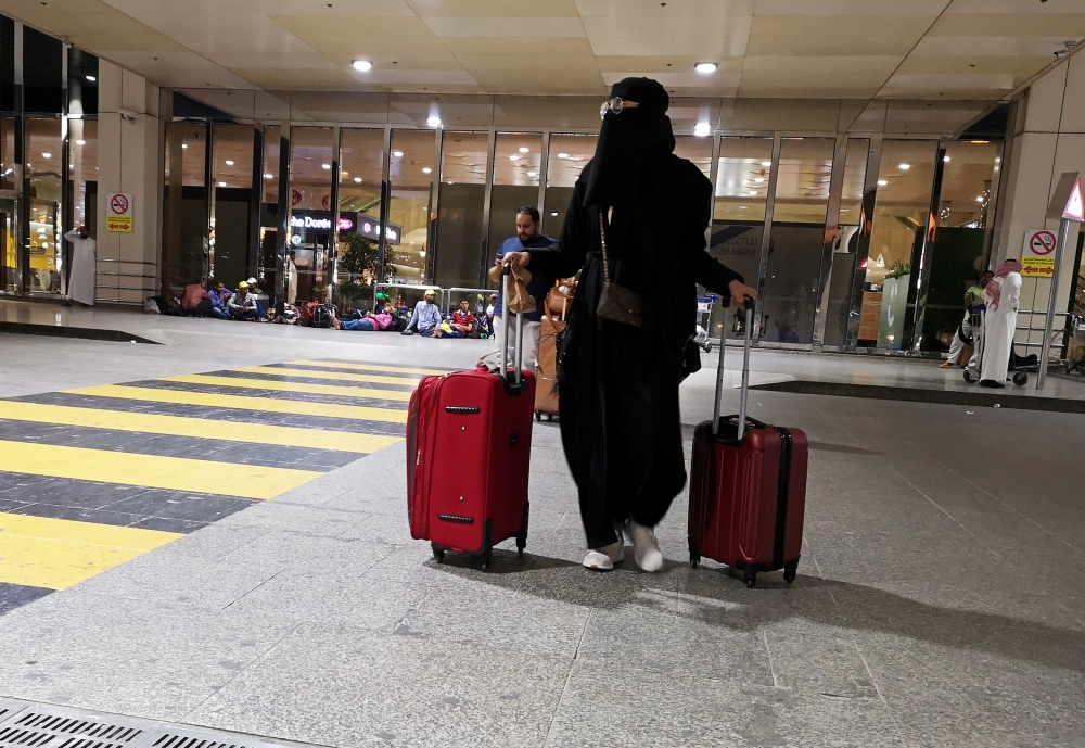 A Saudi woman walks with her luggage as she arrives at King Fahd International Airport in Dammam in this Aug. 5, 2019 file photo — Reuters