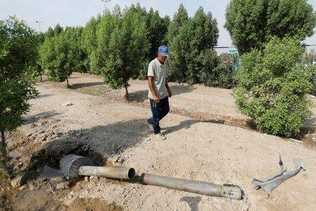 A man looks at a rocket that flew away after a weapons depot of an Iraqi militia group caught fire, in Baghdad, in this file photo. — Reuters