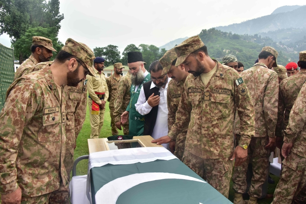 Pakistani soldiers look at a colleague who was killed in cross border shelling during a funeral in Muzaffarabad, the capital of Pakistan-controlled Kashmir, in this Aug. 16, 2019 file photo. — AFP