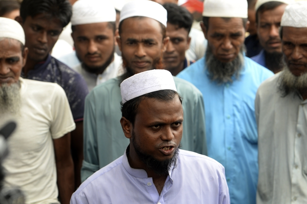 Sayed Ullah, center, a representative of the Rohingya community, speaks to the press as local leaders give their reaction to a repatriation plan for refugees to return to Myanmar from Bangladesh in the Shalbagan camp in Teknaf on Thursday. — AFP