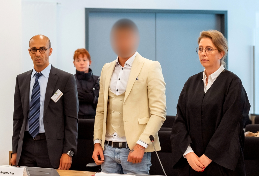Alaa Sheikhi., suspected of being responsible for the stabbing of Daniel H. in Chemnitz, his interpreter and lawyer Ricarda Lang arrive at a court in Dresden, Germany, on Thursday. — Reuters
