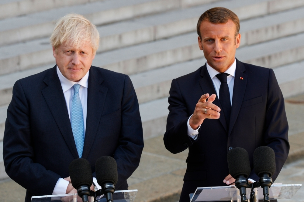 French President Emmanuel Macron, right, gestures as he speaks to the press next to Britain's Prime Minister Boris Johnson, left, prior to their meeting at The Elysee Palace in Paris on Thursday. — AFP