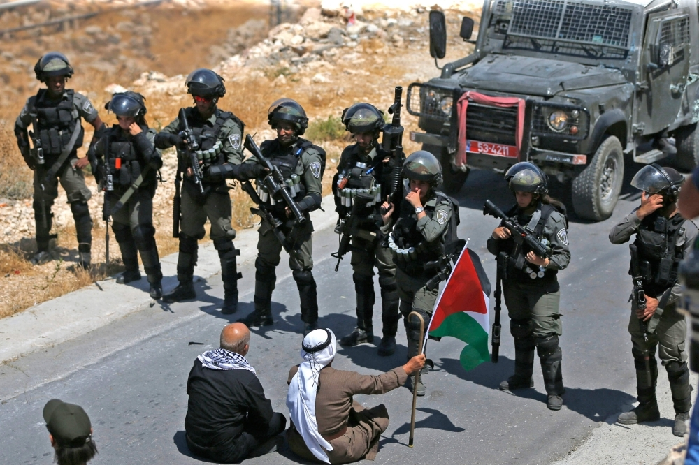 Palestinian protesters sit before Israeli troops during a demonstration against the expropriation of Palestinian land by Israel, in the village of Kafr Malik northeast of Ramallah in the Israeli-occupied West Bank, in this Aug. 16, 2019 file pho. — AFP ABBAS MOMANI