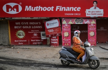 A woman rides her scooter past a Muthoot Finance branch in Ahmedabad, India, on Wednesday. — Reuters