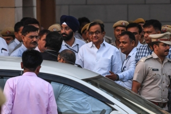 Former Indian Finance Minister Palaniappan Chidambaram, center in white shirt with glasses, leaves a court in New Delhi on Thursday. — AFP