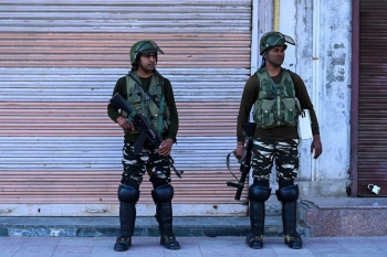 Security personnel stand guard on a street near closed shops in Srinagar, India, on Thursday. — AFP