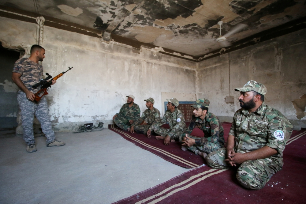 A trainer, member of the paramilitary Popular Mobilization Forces (PMF), explains how to use weapons as part of a military training at the PMF camp in Basra, Iraq, in this Aug. 4, 2019 file photo. — Reuters