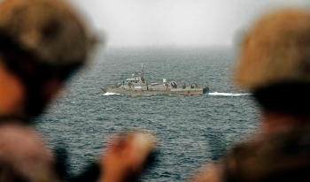 This handout picture taken by the US Navy on Aug. 12, 2019, shows US sailors aboard an amphibious transport dock ship as they keep watch on Iranian fast attack craft in the Strait of Hormuz.  — AFP
